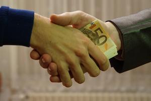fotografía de una persona entregando dinero a otra